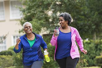 Two women walking outdoors carrying water bottles