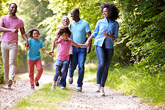 Four adults and two children strolling along a wooded trail
