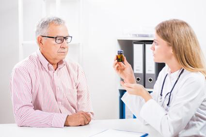 Foto de un paciente que le muestra todas las botellas de sus medicinas a un médico.