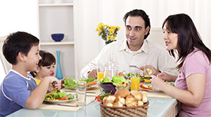 Family sitting at the family table eating a healthy meal.