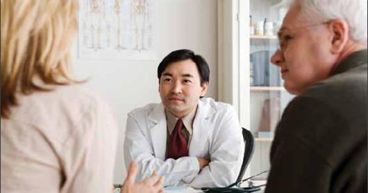 Foto de un médico escuchando a un paciente anciano y a su acompañante.