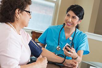 Una mujer teniendo su presión arterial revisado por un profesional de la salud.