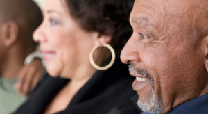 An African American man and a Hispanic woman look interested as they sit next to each other in a row